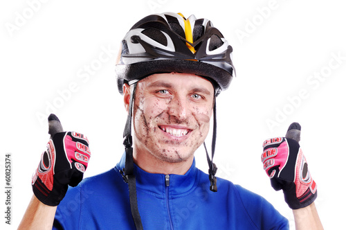 Cros-country cyclist with mud on his happy face