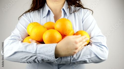 holding a lot of  oranges