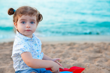 Blu eyes brunette toddler girl playing with sand in beach
