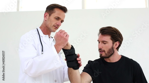 Doctor checking on injured patient in a wrist brace