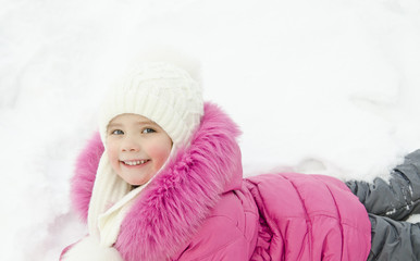 Smiling little girl lying in snow