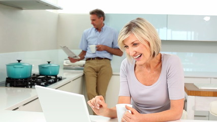 Woman using laptop while her husband is standing reading