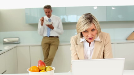 Businesswoman using laptop while husband eats cereal