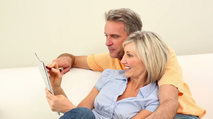 Couple laughing together on the couch doing the crossword puzzle