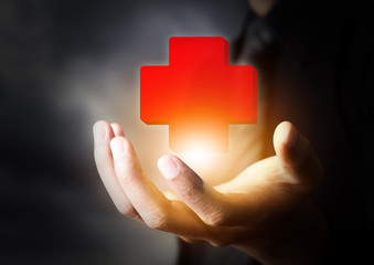 Hand holding First Aid icon, insurance concept