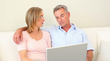 Mature couple looking at laptop together on the couch