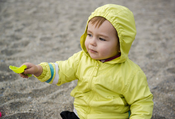 Lovely baby girl playing with plastic shovel on the beach