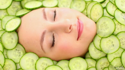 Natural womans face surrounded by cucumber slices