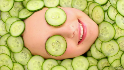 Smiling womans face surrounded by cucumber slices
