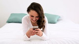 Smiling woman lying on bed texting on her phone