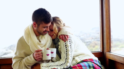 Cute couple cuddling together under a blanket in their ski lodge