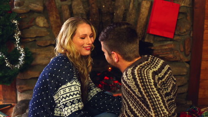 Cute couple celebrating christmas together in front the fire