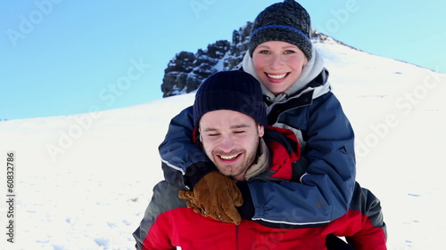 Smiling man giving his girlfriend a piggy back in the snow