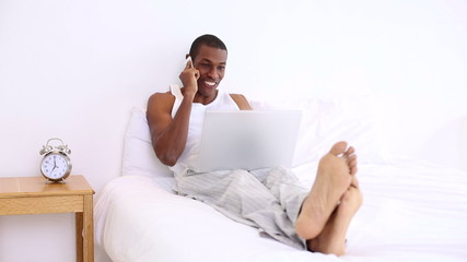 Handsome man lying on bed phoning and using laptop