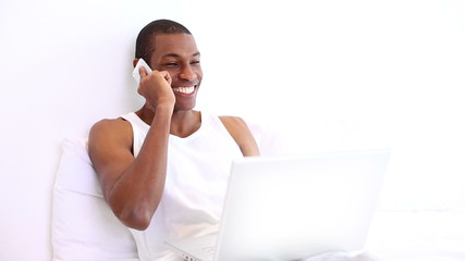 Happy man lying on bed phoning and using laptop