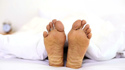 Man wiggling his toes under the covers