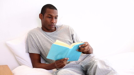 Relaxed man lying on bed reading