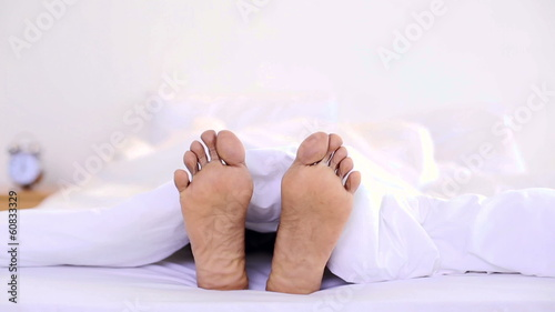 Man wiggling his toes under the duvet
