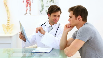 Handsome doctor discussing xray with his patient
