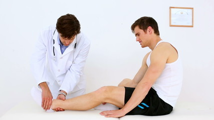 Doctor checking patients injured ankle
