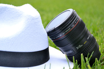 Camera lens and white hat on the grass