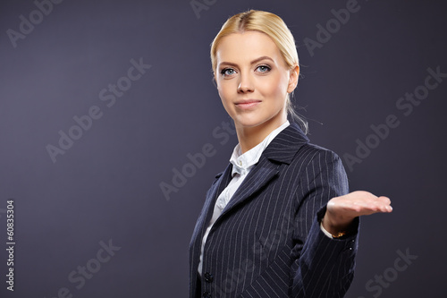 businesswoman presenting something on grey background