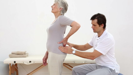 Physiotherapist touching senior patients lower back
