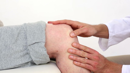 Doctor touching senior patients knee