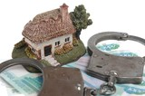 Handcuffs, toy house and white envelope with money isolated clos