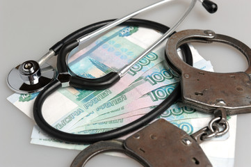 Stethoscope, handcuffs and money on gray