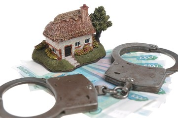 Handcuffs, toy house and white envelope with money isolated