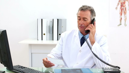Mature doctor talking on the phone at his desk