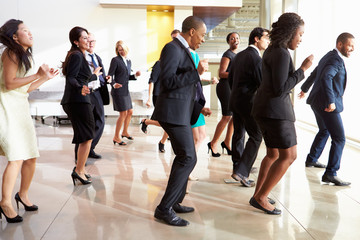Businessmen And Businesswomen Dancing In Office Lobby