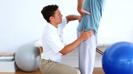 Physiotherapist checking the lower back of patient