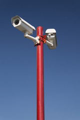 security camera on red pillar,blue isolated
