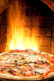 pizza with ham, mushroom and fire flames in oven
