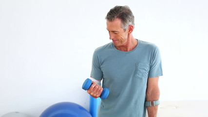 Injured mature patient on crutches lifting dumbbell