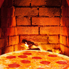pizza with salami and hot brick wall of oven