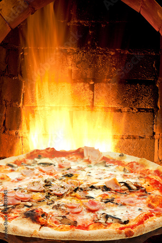 Fotobehang Assortiment pizza with ham, mushroom and fire flames in oven