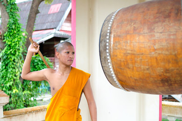 Buddhist monk, hitting the drum in the temple.