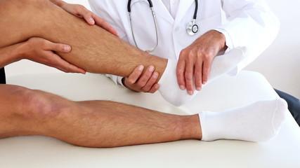Doctor checking sportsmans injured ankle