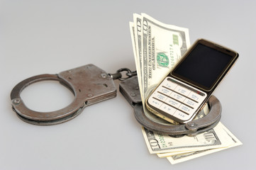 Handcuffs with mobile phone and money on gray