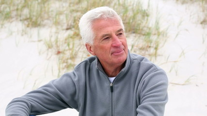 Retired white haired man relaxing on the beach