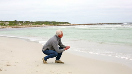 Retired man kneeling on the beach looking out to sea