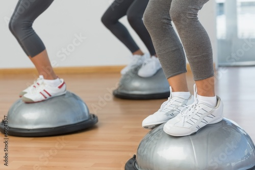 Low section of fit people performing step aerobics exercise