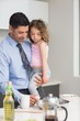 Well dressed father carrying his daughter while preparing food