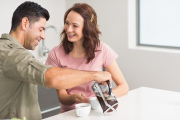 Happy man pouring tea to womans cup in kitchen