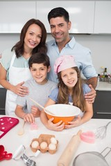 Portrait of family of four preparing cookies in kitchen