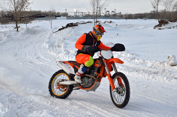 Winter motocross racer on a motorcycle rides in turn of