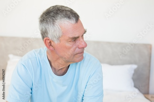 Senior man looking away on bed